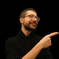 Foto di Emanuele Vaccari che guarda e punta con il dito alla sua sinistra